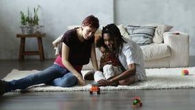 Ευτυχείς γονείς που παίζουν με το γιο μικρών παιδιών στο πάτωμα απόθεμα βίντεο