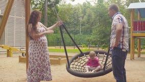 Ευτυχείς γονείς που ταλαντεύονται ένα κοριτσάκι σε μια ταλάντευση φιλμ μικρού μήκους