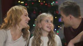 Ευτυχείς γονείς που φιλούν τη λατρευτή κόρη τους στα μάγουλα που κάθεται κάτω από το χριστουγεννιάτικο δέντρο απόθεμα βίντεο