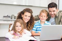 Ευτυχείς γονείς που χρωματίζουν και που χρησιμοποιούν το lap-top με τα παιδιά τους Στοκ φωτογραφία με δικαίωμα ελεύθερης χρήσης