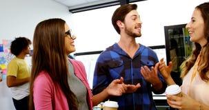 Ευτυχείς γραφικοί σχεδιαστές που αλληλεπιδρούν ενώ έχοντας τον καφέ απόθεμα βίντεο