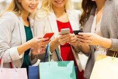 Ευτυχείς γυναίκες με τα smartphones και τις τσάντες αγορών Στοκ εικόνα με δικαίωμα ελεύθερης χρήσης