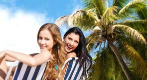 Ευτυχείς γυναίκες που κάνουν ηλιοθεραπεία στις καρέκλες πέρα από τη θερινή παραλία Στοκ Φωτογραφία
