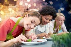 Ευτυχείς γυναίκες που μαγειρεύουν και που διακοσμούν τα πιάτα Στοκ εικόνα με δικαίωμα ελεύθερης χρήσης