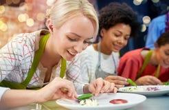 Ευτυχείς γυναίκες που μαγειρεύουν και που διακοσμούν τα πιάτα Στοκ φωτογραφία με δικαίωμα ελεύθερης χρήσης