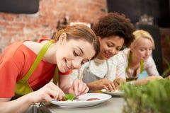 Ευτυχείς γυναίκες που μαγειρεύουν και που διακοσμούν τα πιάτα Στοκ Εικόνες