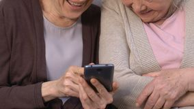 Ευτυχείς γυναίκες που προσέχουν τις αστείες φωτογραφίες στο smartphone και το γέλιο, που θυμούνται από μπροστά απόθεμα βίντεο