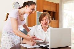 Ευτυχείς γυναίκες που φαίνονται οικονομικά έγγραφα στο lap-top Στοκ φωτογραφία με δικαίωμα ελεύθερης χρήσης