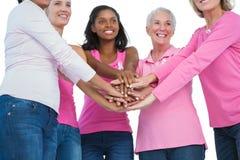 Ευτυχείς γυναίκες που φορούν τις κορδέλλες καρκίνου του μαστού με τα χέρια από κοινού στοκ εικόνα με δικαίωμα ελεύθερης χρήσης