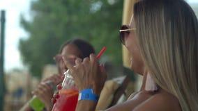 Ευτυχείς γυναίκες στα γυαλιά ηλίου που απολαμβάνουν ένα ποτό στην όμορφη παραλία απόθεμα βίντεο