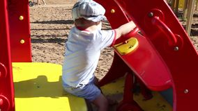 Ευτυχείς γύροι λίγων όμορφοι αγοριών στο ξύλινο αυτοκίνητο παιχνιδιών στην παιδική χαρά φιλμ μικρού μήκους