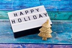 Ευτυχείς διακοπές λέξεων και μικρό χρυσό δέντρο πεύκων που βάζουν στο φωτεινό μπλε ξύλινο πίνακα Στοκ Εικόνα
