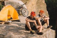 ευτυχείς δοκιμαστικοί ποδηλάτες που τρώνε τα κονσερβοποιημένα τρόφιμα στη στρατοπέδευση στοκ εικόνα με δικαίωμα ελεύθερης χρήσης