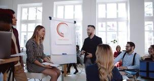 Ευτυχείς ενεργοί multiethnic συνάδελφοι που εργάζονται μαζί, ζωηρή συζήτηση διασκέδασης στο σύγχρονο εταιρικό επιχειρησιακό σεμιν απόθεμα βίντεο