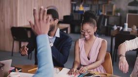 Ευτυχείς επιτυχείς multiethnic επιχειρηματίες που ενώνουν τα χέρια, που ενθαρρύνονται από τον καυκάσιο θηλυκό αρχηγό ομάδας στη σ φιλμ μικρού μήκους