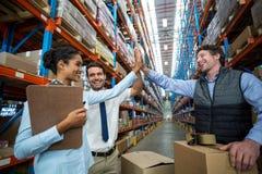 Ευτυχείς εργαζόμενοι αποθηκών εμπορευμάτων που δίνουν υψηλά πέντε στοκ εικόνα