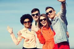 Ευτυχείς εφηβικοί φίλοι στις σκιές που κυματίζουν τα χέρια Στοκ Φωτογραφία