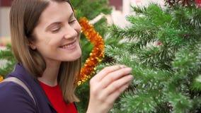 Ευτυχείς εύθυμες διακοσμήσεις Χριστουγέννων αγοράς γυναικών στη λεωφόρο Θηλυκό που επιλέγει faux το χριστουγεννιάτικο δέντρο απόθεμα βίντεο