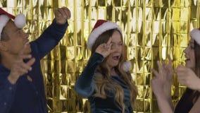 4 ευτυχείς εύθυμοι άνθρωποι σε ένα κόμμα στα κόκκινα καπέλα Άγιου Βασίλη χορεύουν αστείος σε ένα κόμμα Μια ομάδα γελώντας ανθρώπω φιλμ μικρού μήκους