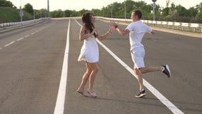 Ευτυχείς, εύθυμοι νέοι που χορεύουν σε έναν κενό δρόμο κίνηση αργή φιλμ μικρού μήκους
