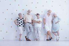 Ευτυχείς ηλικιωμένοι άνθρωποι στα περιστασιακά ενδύματα στο άσπρο στούντιο με το χρυσό στοκ εικόνες