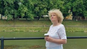 Ευτυχείς ηλικιωμένοι περίπατοι γυναικών κατά μήκος της προκυμαίας και του καφέ κατανάλωσης Ποταμός στο υπόβαθρο απόθεμα βίντεο