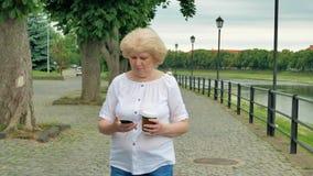 Ευτυχείς ηλικιωμένοι περίπατοι γυναικών κατά μήκος της προκυμαίας χρησιμοποιώντας το smartphone και πίνοντας τον καφέ απόθεμα βίντεο