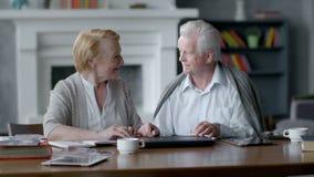 Ευτυχείς ηλικιωμένοι άνδρας και γυναίκα που χρησιμοποιούν τον υπολογιστή Το κλείνουν και εξετάζουν ο ένας τον άλλον απόθεμα βίντεο