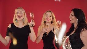 Ευτυχείς θετικές γυναίκες με τα ποτήρια της σαμπάνιας που χορεύουν στο κόκκινο υπόβαθρο απόθεμα βίντεο