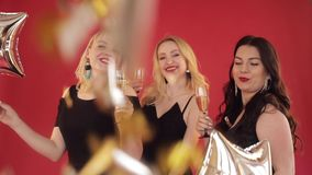 Ευτυχείς θετικές γυναίκες με τα ποτήρια της σαμπάνιας που χορεύουν στο κόκκινο υπόβαθρο φιλμ μικρού μήκους