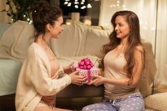 Ευτυχείς θηλυκοί φίλοι με το δώρο Χριστουγέννων στο σπίτι Στοκ Φωτογραφία