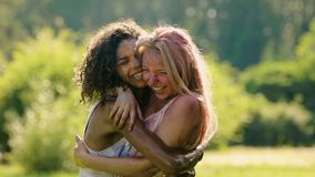 Ευτυχείς θηλυκοί φίλοι που αγκαλιάζουν και που γελούν στο φεστιβάλ θερινού χρώματος, σε αργή κίνηση απόθεμα βίντεο
