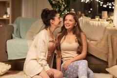 Ευτυχείς θηλυκοί φίλοι που κουτσομπολεύουν στο σπίτι Στοκ εικόνα με δικαίωμα ελεύθερης χρήσης