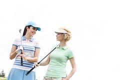 Ευτυχείς θηλυκοί παίκτες γκολφ που εξετάζουν ο ένας τον άλλον ενάντια στο σαφή ουρανό Στοκ φωτογραφίες με δικαίωμα ελεύθερης χρήσης