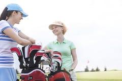 Ευτυχείς θηλυκοί παίκτες γκολφ που μιλούν στο γήπεδο του γκολφ ενάντια στο σαφή ουρανό Στοκ Εικόνες