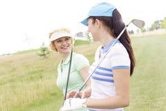 Ευτυχείς θηλυκοί παίκτες γκολφ που μιλούν στο γήπεδο του γκολφ Στοκ Φωτογραφίες