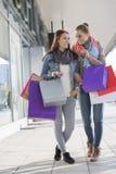 Ευτυχείς θηλυκοί φίλοι που επικοινωνούν φέρνοντας τις τσάντες αγορών στο πεζοδρόμιο Στοκ φωτογραφία με δικαίωμα ελεύθερης χρήσης