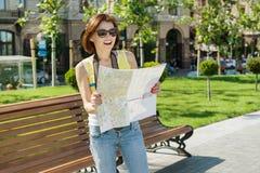 Ευτυχείς κάμερα και χάρτης εκμετάλλευσης ταξιδιού τουριστών γυναικών ανασκόπηση αστική Στοκ Φωτογραφία