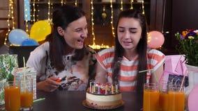 Ευτυχείς κορίτσι και μητέρα εφήβων με το κέικ γενεθλίων στο κόμμα επετείου φιλμ μικρού μήκους