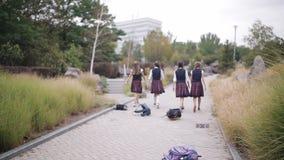 Ευτυχείς μαθήτριες κοριτσιών που ρίχνονται στα χαρτοφυλάκια αέρα που απολαμβάνουν τις διακοπές Ευτυχής φοιτητής πανεπιστημίου στο φιλμ μικρού μήκους