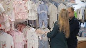 Ευτυχείς μελλοντικοί γονείς που ψωνίζουν στο κατάστημα μωρών φιλμ μικρού μήκους