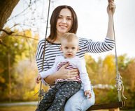 Ευτυχείς μητέρα και αυτή λίγη ταλάντευση μωρών στο πάρκο φθινοπώρου Στοκ εικόνα με δικαίωμα ελεύθερης χρήσης
