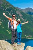Ευτυχείς μητέρα και γιος με τα σακίδια πλάτης υψηλά στα βουνά Στοκ Εικόνα