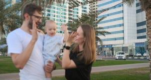 Ευτυχείς μητέρα και γιος οικογενειακών πατέρων που στέκονται σε ένα πάρκο, ο υψηλός-fives-μέγιστος πατέρας παιδιών φιλμ μικρού μήκους