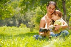 Ευτυχείς μητέρα και γιος που διαβάζουν ένα βιβλίο υπαίθρια στοκ εικόνες