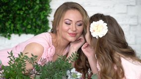 Ευτυχείς μητέρα και κόρη μεταξύ των λουλουδιών, σε αργή κίνηση φιλμ μικρού μήκους