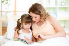 Ευτυχείς μητέρα και κόρη παιδιών που διαβάζουν ένα βιβλίο στοκ φωτογραφία