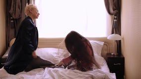 Ευτυχείς μητέρα και κόρη που έχουν την πάλη μαξιλαριών στο κρεβάτι στο σπίτι απόθεμα βίντεο