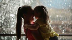 Ευτυχείς μητέρα και κόρη που έχουν τη διασκέδαση στην ημέρα της μητέρας Ο καταρράκτης είναι στο υπόβαθρο Μητέρα που κρατά το παιδ φιλμ μικρού μήκους