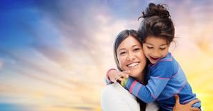 Ευτυχείς μητέρα και κόρη που αγκαλιάζουν πέρα από τον ουρανό βραδιού Στοκ φωτογραφία με δικαίωμα ελεύθερης χρήσης